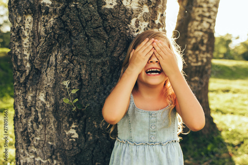Fotomural Horizontal outdoor image of smiling little girl covering her eyes with both hands, playing hide and seek standing next a big tree