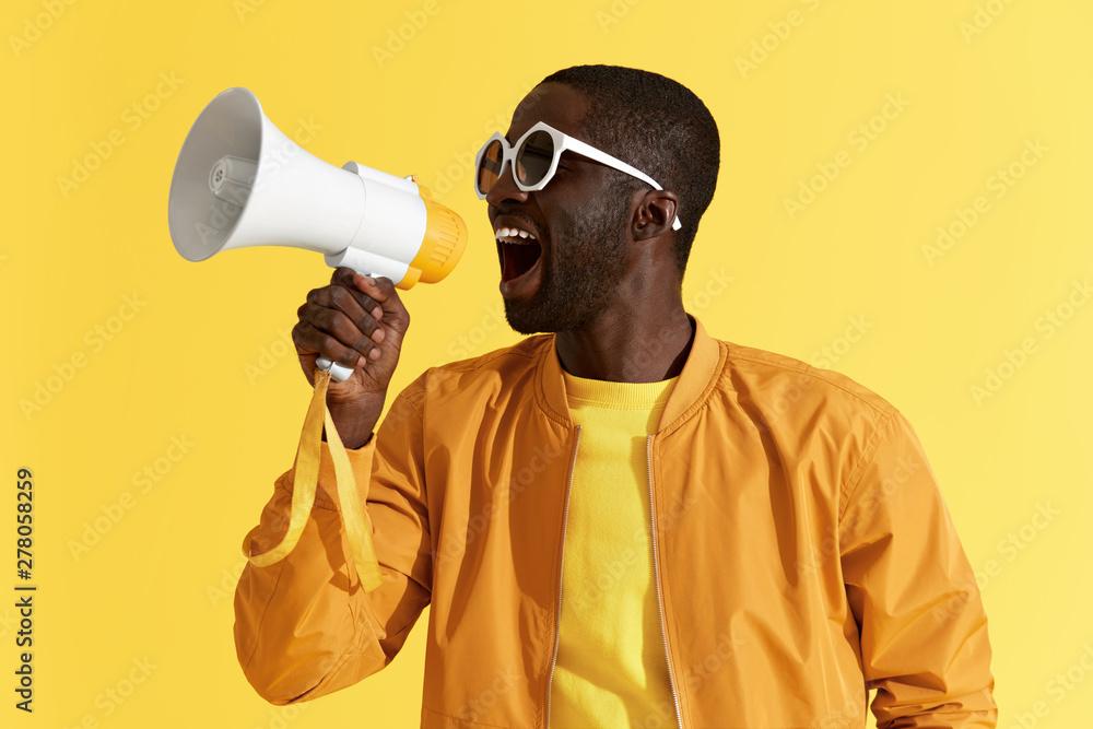 Fototapeta Advertising. Man screaming announcement in megaphone portrait