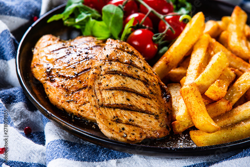 Fotobehang Kip Grilled chicken fillet with french fries on wooden table