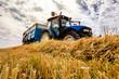Leinwandbild Motiv tractor and trailer during harvest