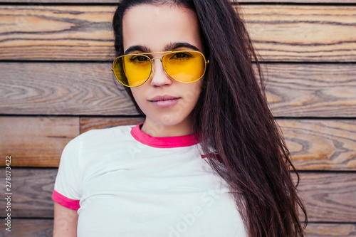 Young self-confident and serious girl student in stylish clothes is posing against the background of a wooden wall and is enjoying first warm summer days Canvas-taulu