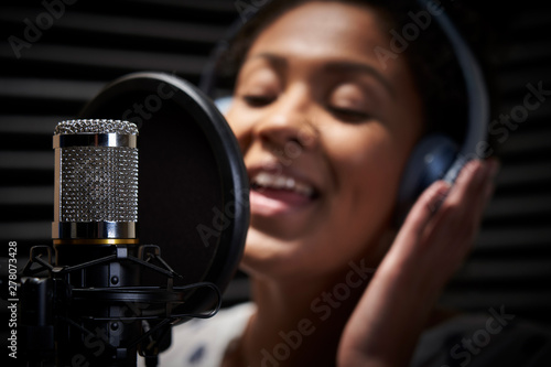 Fotografia Female Vocalist Wearing Headphones Singing Into Microphone In Recording Studio
