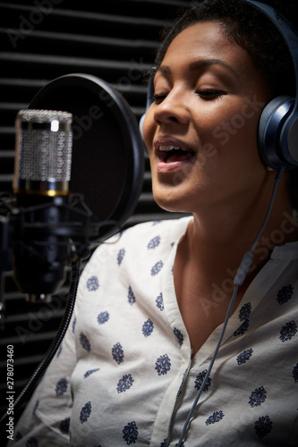 Canvas Print Female Vocalist Wearing Headphones Singing Into Microphone In Recording Studio