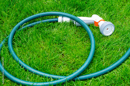 Fotografie, Obraz Green hose for watering lies on grass, lawn