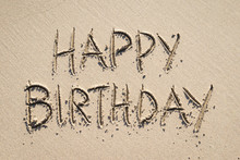 Happy Birthday Message Handwritten In All Capital Letters In Smooth Beach Sand Under Bright Sunlight