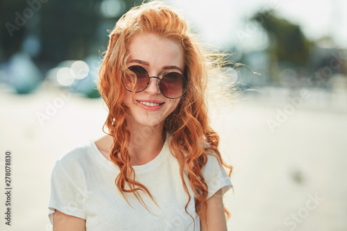 Fototapeta  A beautiful red-haired girl in a white T-shirt and sunglasses walks down the str