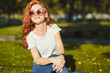 A lovely red-haired girl, warmed by the rays of the sun, is sitting on a lawn and posing for the camera. The girl is wearing a T-shirt with jeans, glasses on her face, and a modern gadget on her arm