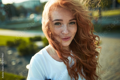 Obraz Portraits of a charming red-haired girl with a cute face. Girl posing for the camera in the city center. She has a wonderful mood and a lovely smile - fototapety do salonu