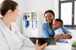 medicine, healthcare and pediatry concept - african american mother with baby son and caucasian doctor with tablet computer at clinic