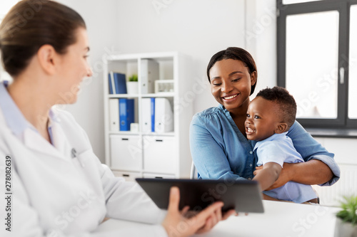 obraz lub plakat medicine, healthcare and pediatry concept - african american mother with baby son and caucasian doctor with tablet computer at clinic