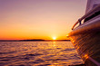 Leinwandbild Motiv Side view Speeding fishing motor boat with drops of water. Blue ocean sea water wave reflections at the sunset. Motor boat in the blue ocean. Ocean yacht. Sunset at the sailboat deck