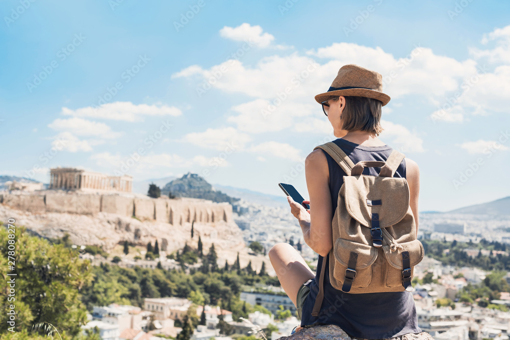 Fototapety, obrazy: Young woman using smart phone in Athens with Acropolis at the background. Traveler girl enjoying vacation in Greece. Summer holidays, vacations, travel, tourism, technology concept.