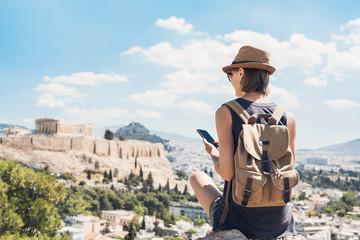 Mlada žena koja koristi pametni telefon u Ateni s Akropolom u pozadini. Djevojka putnica uživa na odmoru u Grčkoj. Ljetni praznici, odmori, putovanja, turizam, tehnološki koncept.