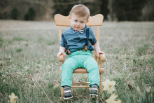 Boy Sitting On Chair On Green Grass Field
