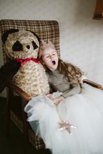 Girl Sitting In Chair With Teddy Bear