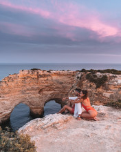 Man And Woman Sitting On Cliff