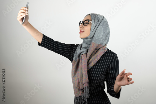 young beautiful Muslim woman in glasses wearing turban hijab, headscarf holding Canvas Print