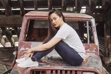 Young Woman Sitting On Hood Of Rusted Truck