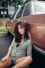 Woman Leaning On Brown Sedan