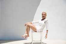 Beautiful Happy Woman In Her Forties Portrait White On White Background Chair And Clothing.