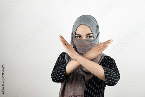 Fotomural young attractive Muslim student wearing turban hijab headscarf saying no to war