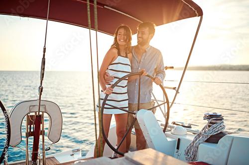 Obraz Romantic couple on boat together enjoy at sunset on vacation. - fototapety do salonu