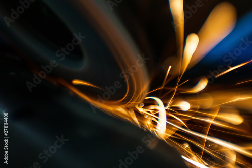 Worker cutting, grinding and polishing motorcycle metal part with sparks indoor workshop. Super macro close-up.