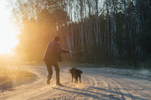 Man With Active Happy Black Dog Playing On The Road Forest Park During Sunset Or Sunrise