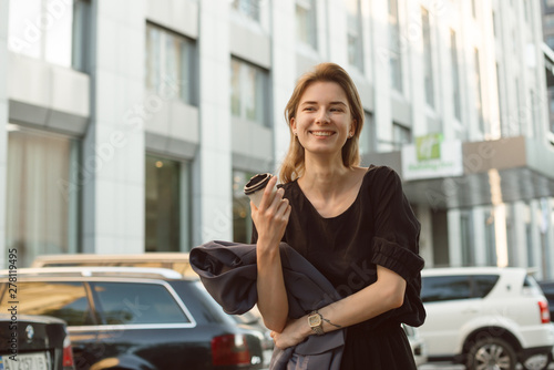 Attractive caucasian girl laughing and feeling happy outside in the urban scenery drinking coffee Wallpaper Mural