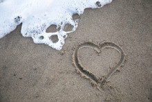 Heart In Sand With Wave Close Up