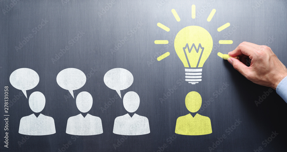 Fototapeta Finding solution during meeting communication. Businessman drawing people and lightbulb on chalkboard.