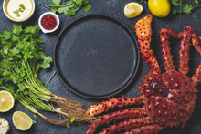 Food Background With Empty Black Plate, Fresh King Crabs, Lemons And Herbs. Top View, Copy Space