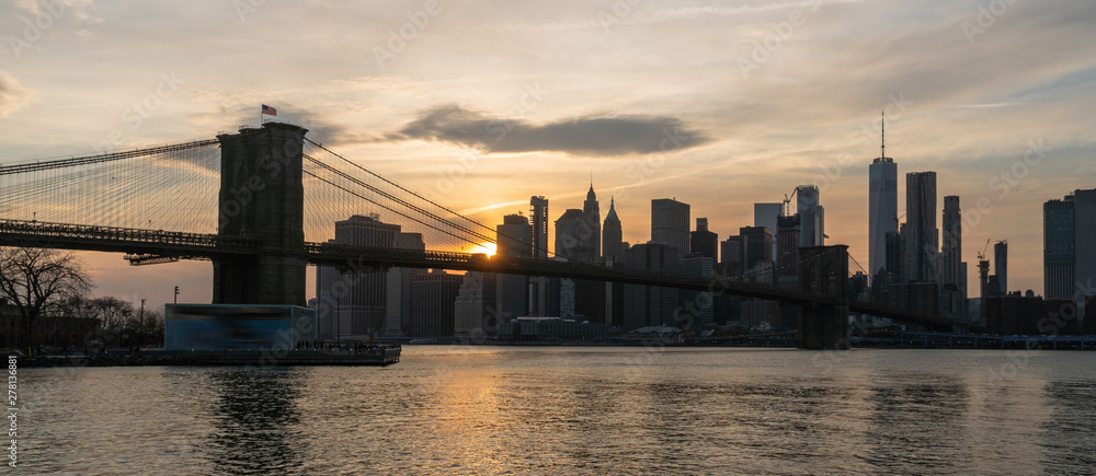 Fototapeta Banner and cover scene of New york Cityscape with Brooklyn Bridge over the east river at the sunset time, USA downtown skyline, Architecture and transportation concept