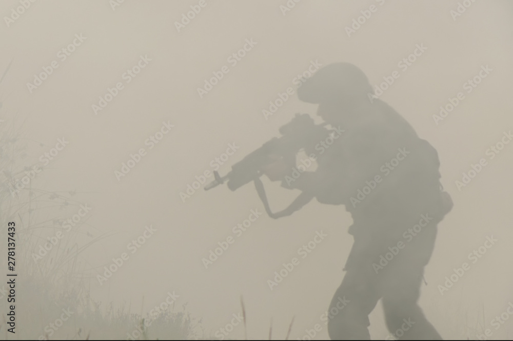 Fototapety, obrazy: Military with a gun in his hands and in a helmet moves cautiously through the smoke and thickets