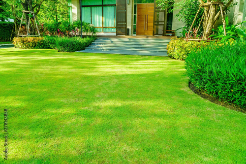 Foto auf Leinwand Garten Green grass, Modern house with beautiful landscaped front yard, Lawn and garden blur background., The design concept for background, garden with green lawn and garden