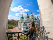A young girl wearing a black leather jacket standing in the bell tower with a view on St Sophia Cathedral behind her, Kiev Ukraine. Girl is enjoying her time and beautiful weather.