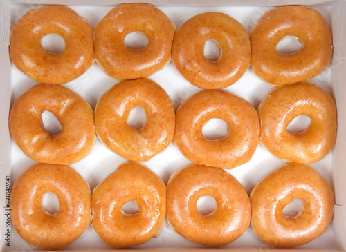 Fototapeta Top view flat lay of plain glazed donuts in a white box isolated. One dozen donuts. The original glazed donut has remained peoples favorite throughout history. obraz