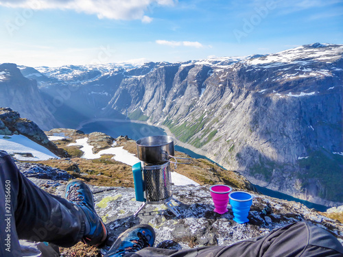 A camping stove, pot with boiling water on it and two cups placed on the ground, ready to prepare tea with view on Ringedalsvatnet lake, Norway Fototapeta