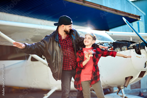 Obraz na plátně young dad and his boy standing together with hands apart like airplane wings, smiling and looking at each other, with toy plane, glad to spend together father's day, came to see aircrafts to hangar