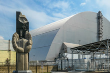 Chernobyl/Ukraine - 04 23 2018: A Monument In Front Of The Reactor 4 Chernobyl, Ukraine. Monument Consists Of Two Hands Holding The Reactor In Them. In The Back There Is Sarcophagus Over Unit 4.
