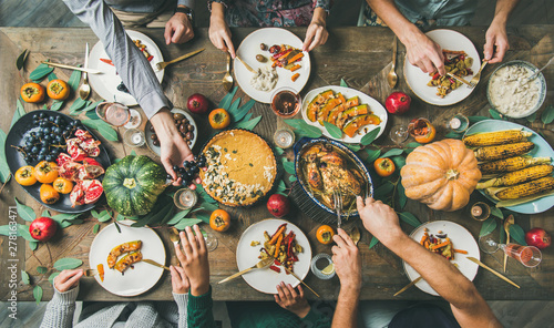Obraz Thanksgiving, Friendsgiving holiday celebration. Flat-lay of friends feasting at Thanksgiving Day table with turkey, pumpkin pie, roasted vegetables, fruit, rose wine, top view - fototapety do salonu
