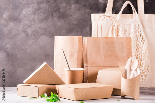 Obraz Catering and street fast food paper cups, plates and containers. Eco-friendly food packaging and cotton eco bags on gray background with copy space. Carering of nature and recycling concept. - fototapety do salonu