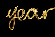 Long Exposure Photograph Of Metallic Gold Colour Spelling The Word 'year' Against A Black Background. Light Painting Photography, Happy New Year Series.