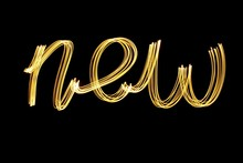 Long Exposure Photograph Of Metallic Gold Colour Spelling The Word 'new' Against A Black Background. Light Painting Photography, Happy New Year Series.