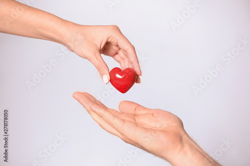 Fotografie, Obraz  Woman giving red heart to man on white background, closeup