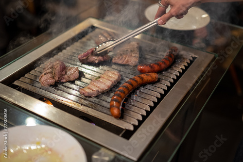 Fotografie, Obraz  different types of meat, beef steaks and pork sausages, cooked on a grill