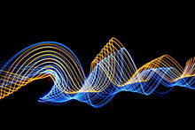 Long Exposure Photograph Of Neon Electric Blue And Gold Colour In An Abstract Swirl Parallel Lines Pattern Against A Black Background. Light Painting Photography.