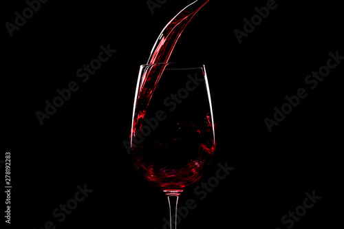 Red wine pouring into a wine glass, over black background, horizontal image