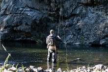Fisherman Standing In The River And Fly Fishing