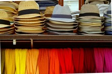 Several Straw Hats And Colorful Scarves For Sale At An Outdoor Market In Verona, Italy. Group Of Colored Hats Showcase Perspective Market Shop. Colors Of Textiles.